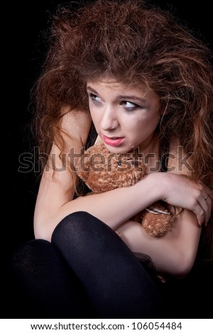Frightened crying girl holding a toy - stock photo