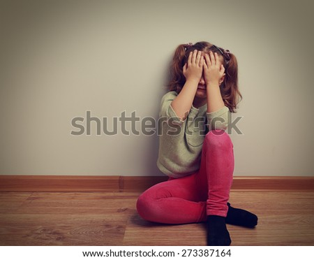 Frightened crying kid girl sitting on the floor with closed face the hands. Vintage closeup portrait - stock photo