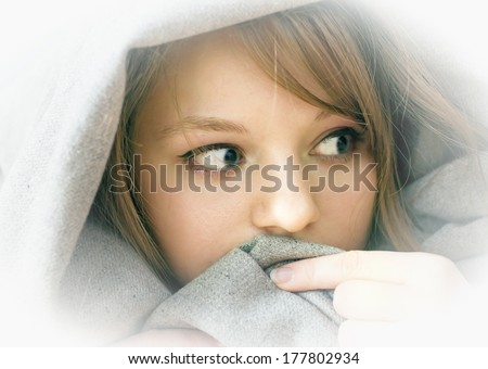 frightened girl lying under a blanket, in the house - stock photo