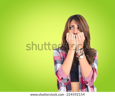 Frightened girl over green background - stock photo