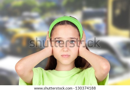 Frightened girl with ears plugged with many cars of background - stock photo