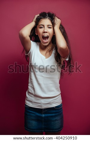 Frightened girl with long brunette hair on red background