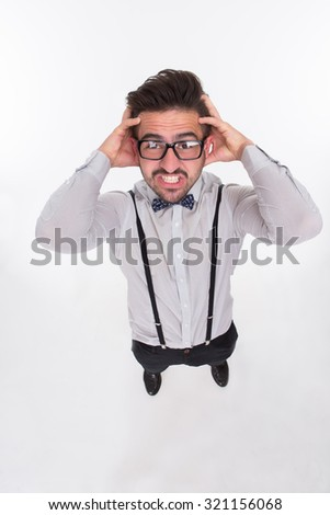 Frightened hipster man touching hishead with both hands in studio. Disappointed man looking directly at the camera. - stock photo