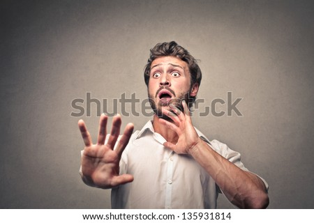 frightened man defends himself with his hands - stock photo