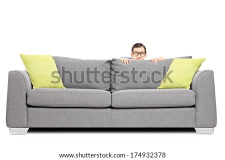 Frightened man hiding behind a sofa isolated on white background - stock photo