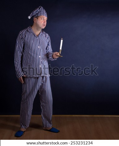 frightened man in pajamas with candle  - stock photo