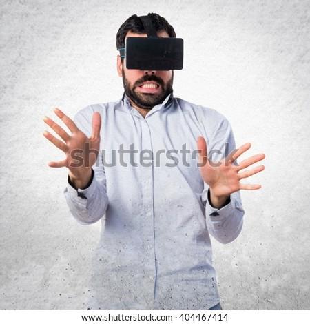 Frightened man using VR glasses - stock photo