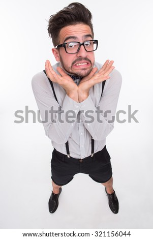 Frightened man with surprised face looking at the camera. Stylish man in glasses dreaming of hiding somewhere isolated on white background. - stock photo