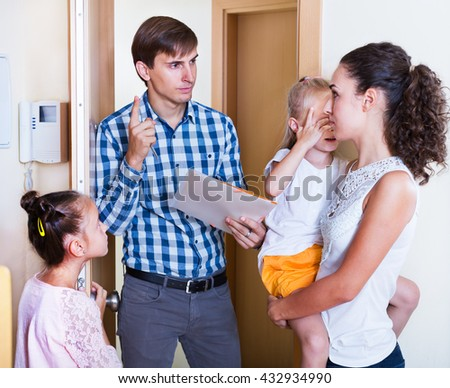 Frightened mother with two kids receiving a debt collector at a doorway