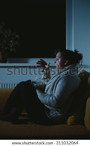 Frightened overweight woman watching horror movie dropping popcorn - stock photo