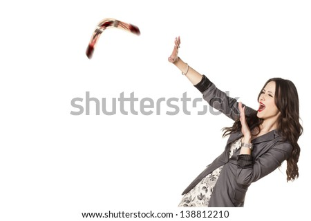 frightened woman defending herself with her ??hands from the boomerang which she threw to someone else - stock photo