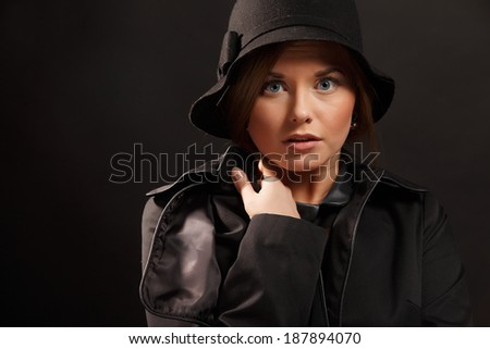 frightened woman looking at camera over black background