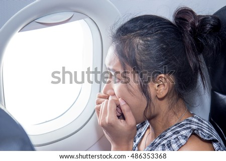 frightened woman looking out an airplane window