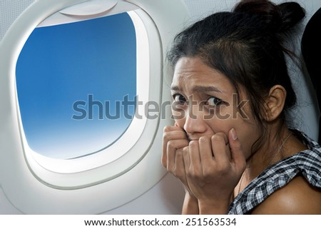 frightened woman sitting at the window of the plane - stock photo