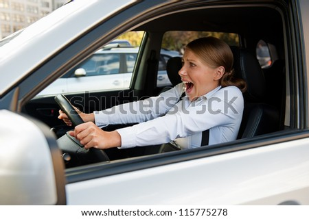 frightened woman sitting in the car and holding for the wheel - stock photo