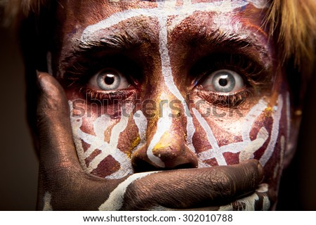 Frightened woman with tribal face painting and blue eyes art holding her mouth with a hand and not allowing herself to scream or talk - stock photo