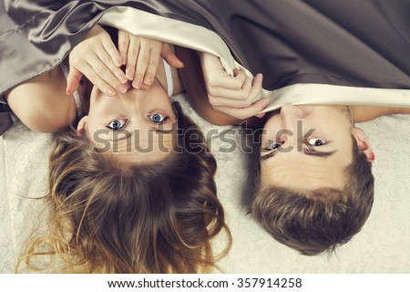 Frightened young couple under the sheets - shock concept - stock photo