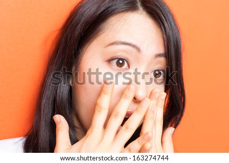 frightened young woman against orange background  - stock photo