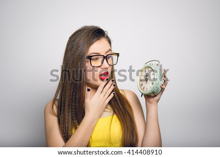 frightened young woman looking at retro alarm clock in yellow clothes close-up isolated - stock photo