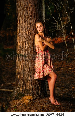 Frightened young woman standing in the woods, on a dark red and Orange, background - stock photo