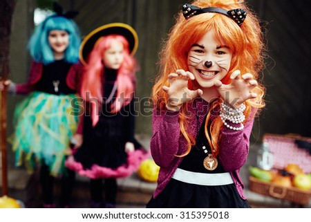 Frightening girl in Halloween costume looking at camera with two friends on background - stock photo