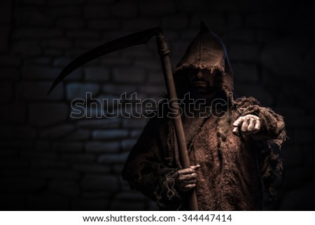 Frightful epitome of death is standing with a scythe. The man is pointing his finger forward with treats. He is very serious. Copy space in left side - stock photo