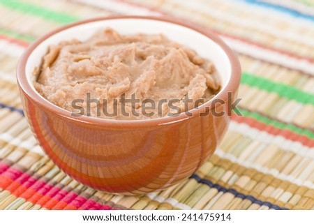 Frijoles Refritos - Bowl of Mexican refried beans on a colourful background.