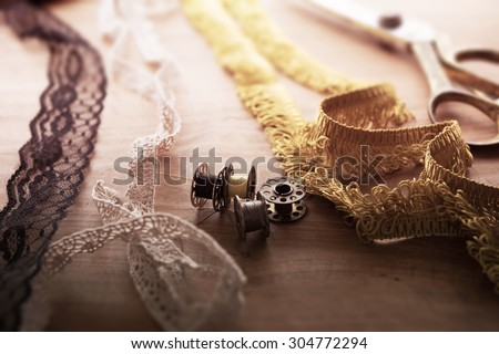 Fringe or lace tapes and silk trimmings with gold (brass) scissors and old sewing machine bobbins on a old grungy work table. Tailor's work table. textile or fine cloth making.Shallow depth of field. - stock photo