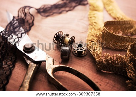 Fringe or lace tapes and silk trimmings with gold (brass) scissors and old sewing machine bobbins on a old grungy work table. Tailor's workbench. textile or fine cloth making.Shallow depth of field. - stock photo