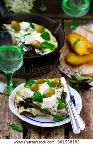 fritatta with eggplants, cheese and olives. style rustic. selective focus