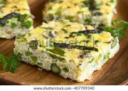 Frittata made of eggs, green asparagus, pea, blue cheese, parsley and brown rice, photographed with natural light (Selective Focus, Focus on the asparagus head on the frittata)