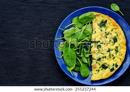 Frittata with chicken and spinach and fresh spinach on a black background. tinting. selective focus - stock photo