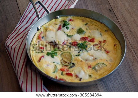 Frittata with Grilled Summer Vegetables baked in stainless steel pan, served in the garden on summer sunny morning. Idea for Breakfast. Summer Meal.
