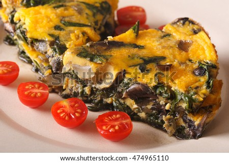 Frittata with spinach and mushrooms on a plate close-up. horizontal