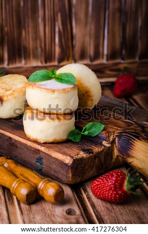 Fritters of cottage cheese with strawberries, sugar powder and mint on wooden background. Selective focus