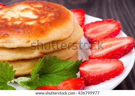 fritters on a plate with strawberries wooden background