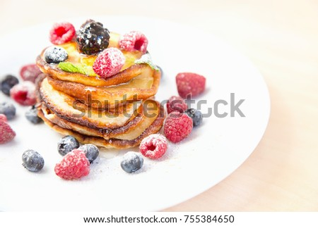 Fritters with fresh berries and honey. Pancakes with fresh strawberries, blueberries, raspberries, maple syrup and honey for breakfast.