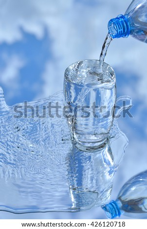 From a plastic bottle the water is flowing in a glass Cup on the background of blue sky - stock photo