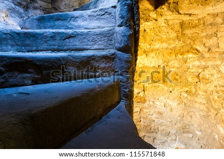 From cold to warm light in stone staircase - stock photo