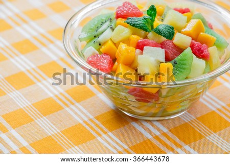 From right side of the frame glass bowl with fruit salad of mango, pineapple, grapefruit, banana and kiwi, left empty space on yellow checkered tablecloth. Fruit exotic salad. Daylight. Horizontal.