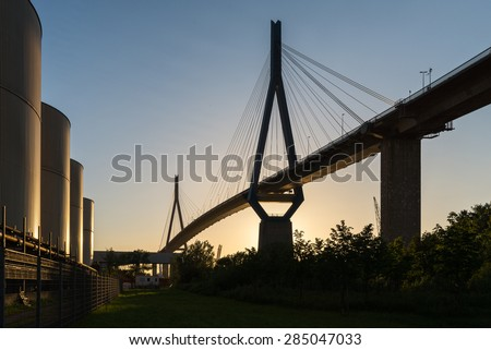 From sunset illuminated Koehlbrand bridge in the harbor of Hamburg. The bridge is an important Cable-stayed bridge and a landmark in Hamburg. It crosses the Elbe river in a height from 315m