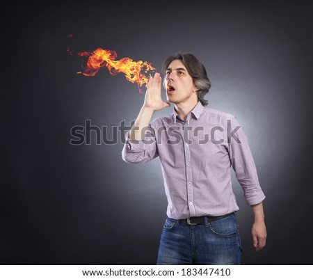 From the mouth of a man a fire erupts. Men suffering from heartburn. - stock photo