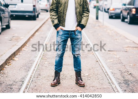 From the neck down view of young fashionable man outdoor in the city with his hands in his pocket - stock photo