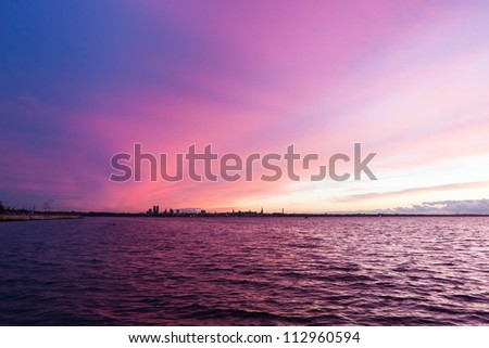 From the sea silhouette of tallinn with fire sea sunset - stock photo