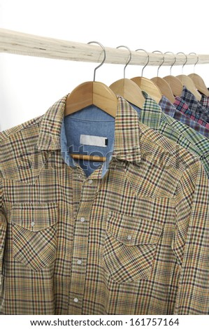 From view Variety of Men's different sleeved plaid cotton on a wooden hanger - stock photo