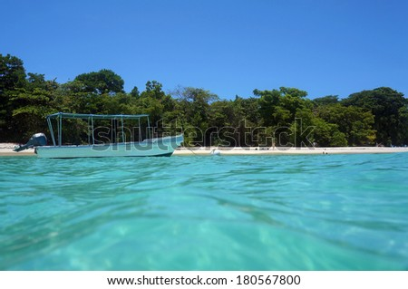 From water surface, boat on mooring buoy near an untouched tropical beach with few tourists, Caribbean sea - stock photo