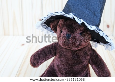 Front and slightly to the right view of the dark brown bear,wears white lace edge and black witch hat,on wood background - stock photo