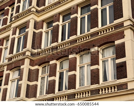 Front beautiful old house facade from red brick with white yellow window frame. Vintage building. Netherlands