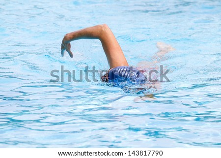 Front crawl swimmer in pool