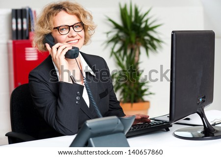 Front desk lady attending call and working on computer - stock photo